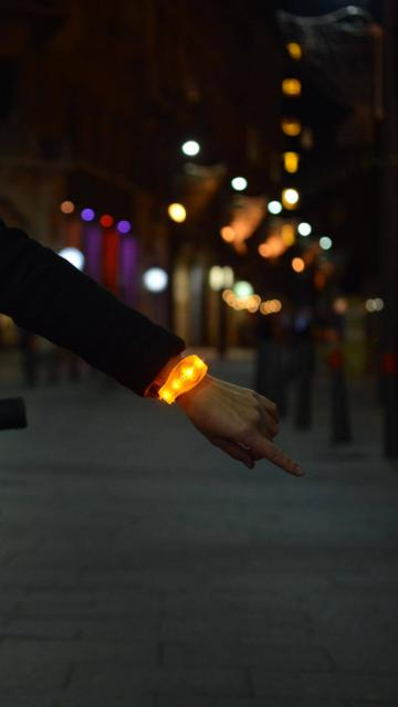 Female cyclist in the dark wearing Useeme Bike Turn Signal Wristbands